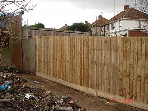 A NEW LONG STRETCH OF CLOSE BOARDED FENCING WITH BARGE BOARDS